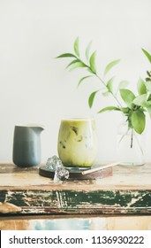Iced matcha latte drink in glass, white wall and plant branches at background, copy space. Summer refreshing beverage cold drink