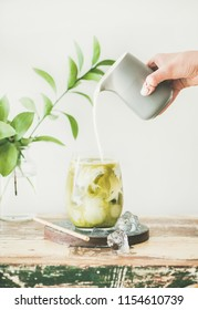 Iced matcha latte drink in glass with coconut milk pouring from pitcher by woman's hand, white wall and plant branches at background, copy space. Summer refreshing beverage cold drink