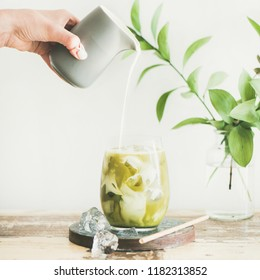 Iced matcha latte drink in glass on board with coconut milk pouring from pitcher by hand, white wall and plant branches at background, copy space, square crop. Summer refreshing beverage cold drink