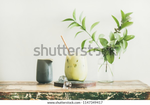 Iced matcha latte drink in glass with coconut milk pouring from pitcher by woman's hand, white wall and plant branches at background, horizontal composition. Summer refreshing beverage cold drink