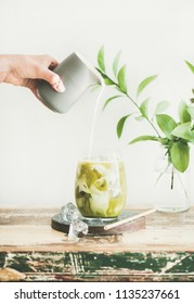 Iced matcha latte drink in tumbler glass with coconut milk pouring from pitcher by hand, white wall and green plant branches at background, copy space. Summer refreshing vegan beverage cold drink