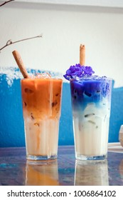 Iced milk tea and butterfly pea latte with cinnamon stick on table and paint blue color wall background.