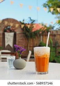 Iced milk tea in modern glass with natural garden view, Thailand.