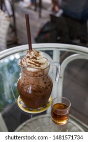 Iced mocha coffee with whip cream topping and syrup on table