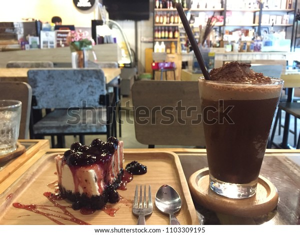 Iced Mocha Frappe with Blueberry cheese cake, the signature menu of a coffee cafe, which are the best seller. They are tasty or delicious for everyone. With blurry background.