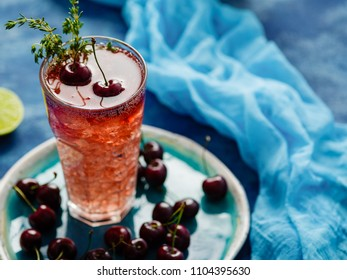 Iced organic cherry lemonade with fresh berries and thyme on the blue table