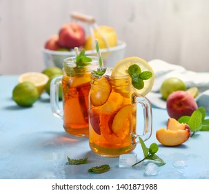 Iced peach tea with lemons, limes and mint with ice cubes, summer refreshment drink, cold juicy fruit tea,  blue background