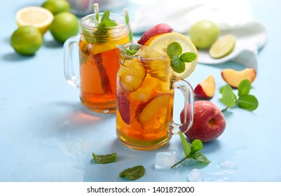 Iced peach tea with  lemons, limes and mint with ice cubes, summer refreshment drink, cold fruit tea,  blue background