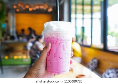 Iced pink milk in hand at coffee shop, beverage