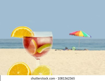 Iced red wine sangria in a glass with beach background. Sliced fruit of orange and lemon. Room for text.