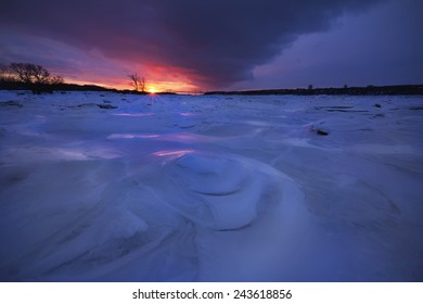 Iced Saint-Laurent river during winter in Quebec with a wonderful sunset
