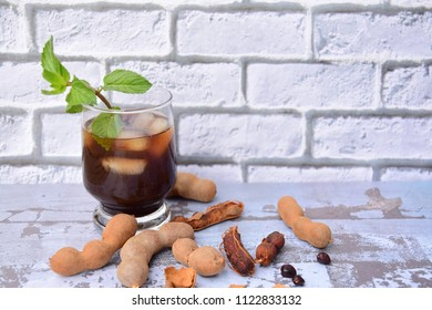 Iced tamarind juice with mint leaf, ripe tamarind fruit and seeds