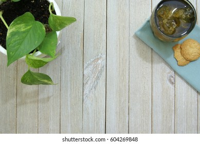 Iced tea and cookies on a green napkin. Pale slatted wood surface or desk from a top down ariel view perspective and a potted house plant vine in the corner.