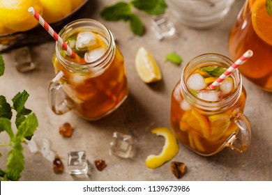 Iced tea with lemon and ice cubes. Served in jar.