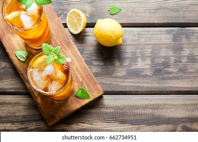 Iced tea with lemon slices, mint and ice cubes on wooden rustic background close up. Homemade refreshing summer drink.