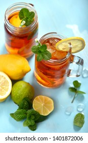 Iced tea with lemons, limes and mint with ice cubes, summer refreshment drink, cold fruit tea,  blue background