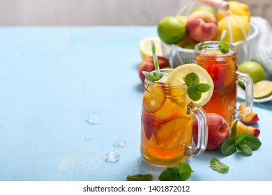 Iced tea with peach, lemons, limes and mint with ice cubes, summer refreshment drink, cold fruit tea,  copy space background
