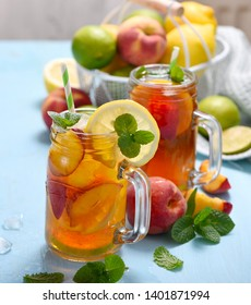 Iced tea with peaches, lemons, limes and mint with ice cubes, summer refreshment drink, cold fruit tea,