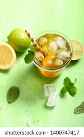 Iced tea, summer refreshment drink or cocktail with lemons and limes, top view grenn background