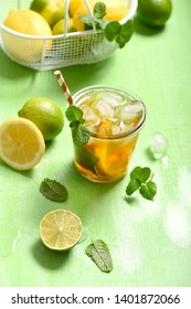 Iced tea, summer refreshment drink or cocktail with lemons and limes, on green background
