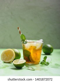Iced tea, summer refreshment drink or cocktail with lemons and limes, copy space background