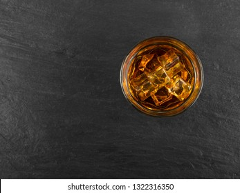 Iced Whiskey Glass on Natural Black Stone Background Close Up and Top View. Luxury Bourbon with Ice Cubes, Cold Brandy, Whisky or Liquor with Place for Text