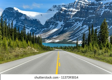 Icefields Parkway at Bow Lake - A Spring evening view of Icefields Parkway extending towards Bow Lake, with BowCrow Peak, Crowfoot Glacier and Crowfoot Mountain rising high behind, Banff National Park