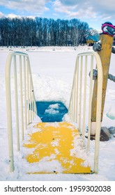 The ice-hole for winter swimming in harsh conditions. The yellow staircase with railing leading to ice cold water.