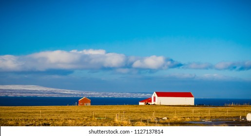Icelalndic farm house and shed with bright red roof and snow cap