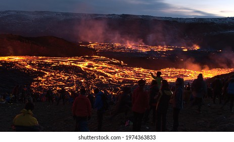 Grindavík, Iceland - 03-29-2021: Recently started volcanic eruption at Fagradalsfjall in Geldingadalir valleys with glowing streams of lava and the silhouettes of people enjoying the view.