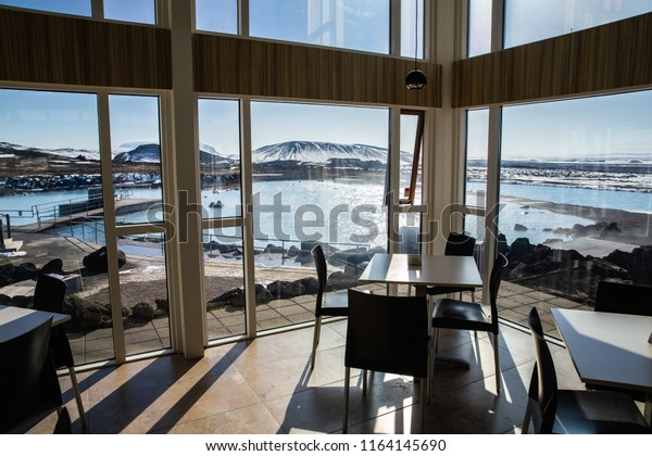 Iceland - April 2018: A scenic view of the main pool of Myvatn Nature Bath in evening time viewed through the glass from inside the dining hall
