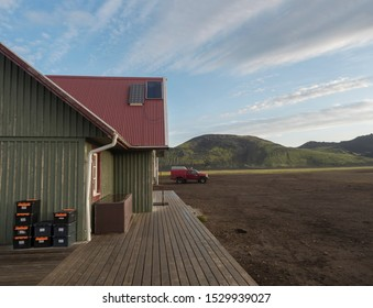 Iceland, Fjallabak Nature Reserve, August 1, 2019: Tourist hut at Alftavatn camping site with supplies boxes, red off-road car and green hills background. Part of famous Laugavegur hiking trail