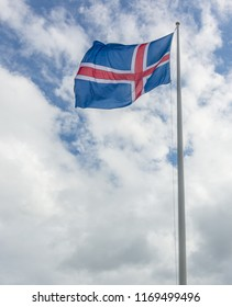 Iceland flag of red and white cross on blue backgroumd hanging proudly in the windy Icelandic weather