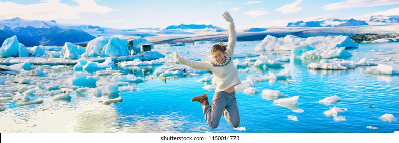 Iceland Jökulsárlón Glacier Lagoon tourist woman jumping of happiness - Icelandic touristic destination popular attraction. Panoramic banner.