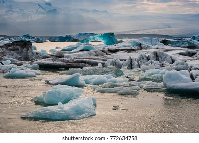 Iceland ice lagoon/Glittering deep blue clear iceberg floating in the Jökulsárlón ice lagoon in Iceland with the hazy glacier Vatnajökull in the backdrop.