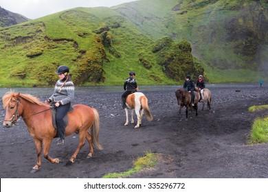 Iceland - June 19, 2015: Skogafoss waterfall with horses and jockeys
