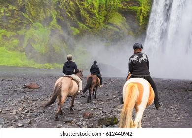 Iceland - June 19, 2015: Skogafoss waterfall with horses and jockeys.