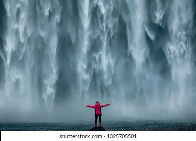 Iceland landscape photo of brave girl who proudly standing with his arms raised in front of water wall of mighty waterfall.