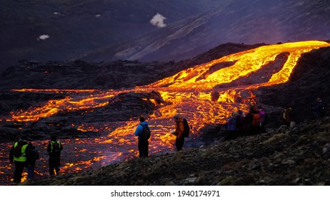Grindavík, Iceland - March 20th, 2021: Onlookers watch an active lava river flowing from a small volcanic eruption in Mt Fagradalsfjall has started, only about 30 km away from Reykjavík.