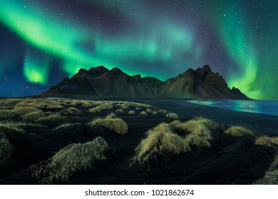 Iceland night landscape amazing northern light in vestrahorn mountain with black sand dunes at stokksnes