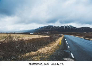 Iceland road landscape with clouds and amply field