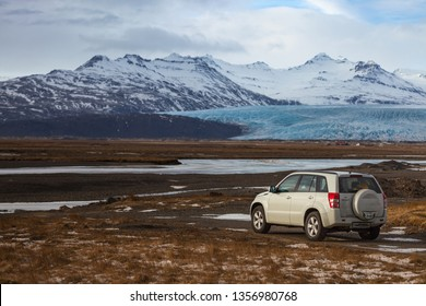 Iceland Scenery (Skaftafell National Park) - a white SUV car and the view of mountain and Vatnajokull Glacier of Skaftafell National Park.