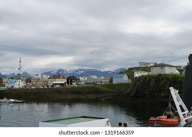 Stykkishólmur, Iceland, viewed from Ferry Baldur. Colourful town by the sea in front of snow covered mountains