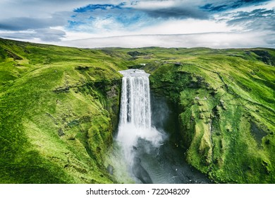 Iceland waterfall Skogafoss in Icelandic nature landscape. Famous tourist attractions and landmarks destination in Icelandic nature landscape on South Iceland. Aerial drone view of top waterfall.