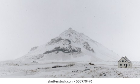 Iceland winter landscape, snowed mountain with white house in the foreground. Snowing conditions.