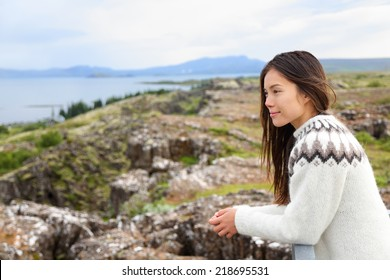 Iceland - woman in Icelandic sweater looking at Thingvellir place of Althing, the first parliament in the world. Girl at tourists destination sightseeing.