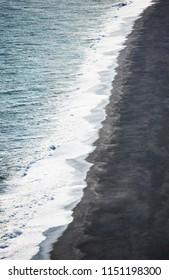 Icelandic coastline. Iceland black sand. Ocean and black sand coast. Geometry coastline in vertical photo. White waves. Vik, Iceland. South Iceland landscape. Black, white, blue landscape.
