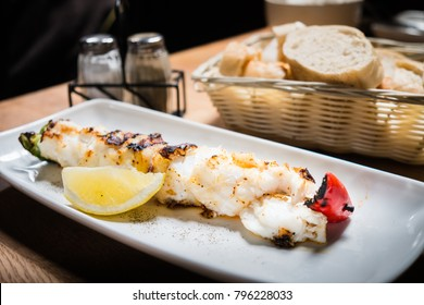 Icelandic cuisine, Grilled or roasted icelandic cod fish with lemon on white dish or plate and a bottle of salt, pepper bottle and toast or bread tray in the background, healthy food.
