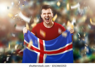 Icelandic fan, fan of a man holding the national flag of Iceland in his hands. Soccer fan in the stadium.