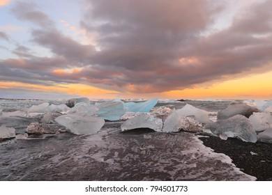 Icelandic glacier Jokulsarlon with icebergs on the beach at sunset